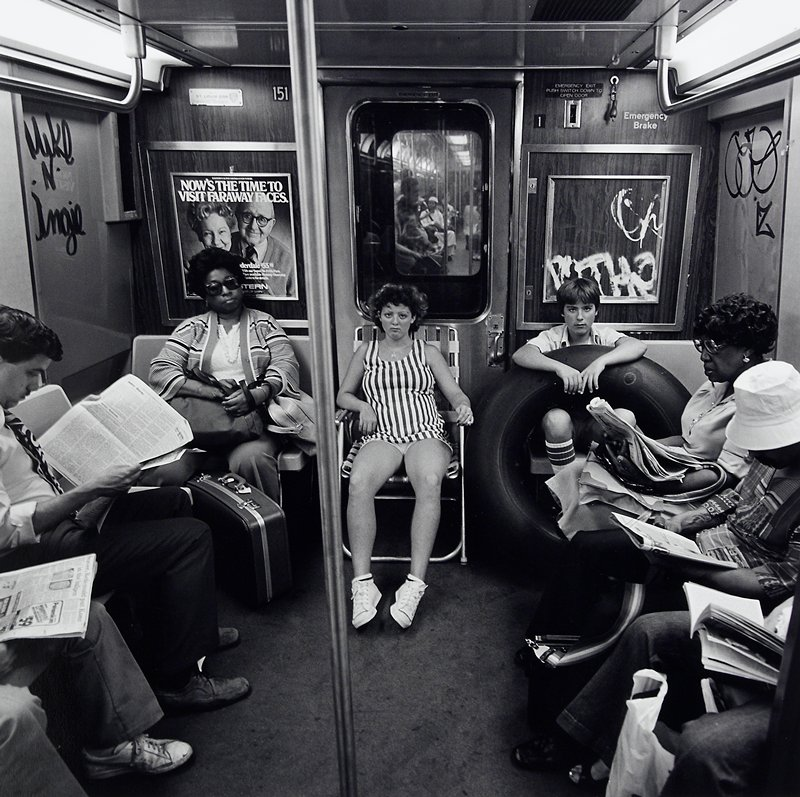girl wearing shorts and striped tank top seated in lawn chair and boy with arms resting on an innertube seated next to girl in a subway car; both looking at camera; other figures at L and R