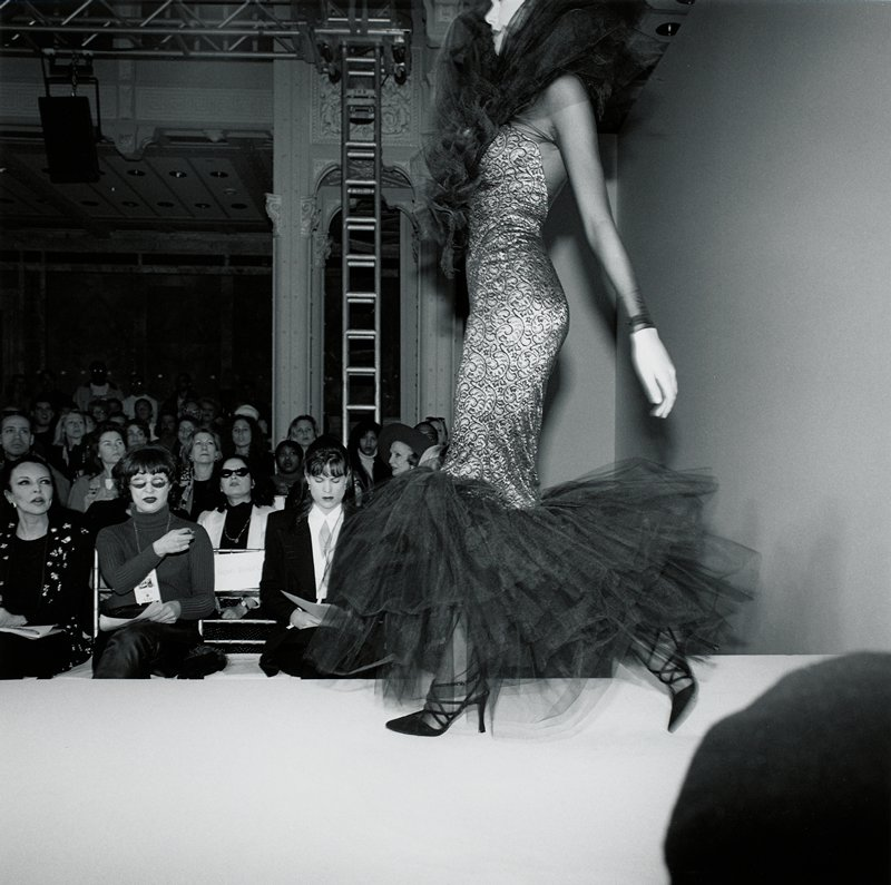 model in profile, wearing a sheath dress with large netting and ruffles at hem and collar; show audience in background at L