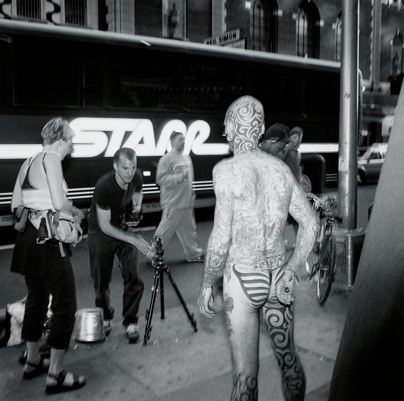man, seen from back, wearing a g-string, with tattoos over his body; photographer setting up a tripod in front of him, at L; bus in street behind figures