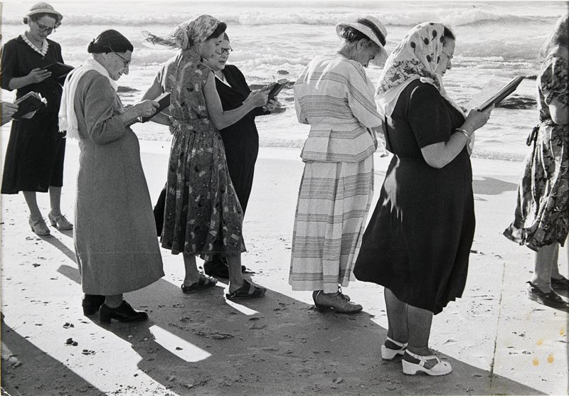 group of women wearing dresses standing on a beach holding open books