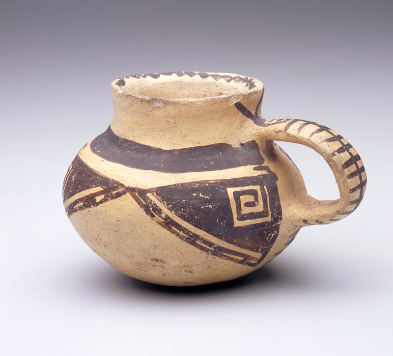 Small round-bodied vessel with short neck, wide mouth, handle and round bottom; brown geometric designs on shoulder; chained brown design on rim; face with linear decorations below on handle