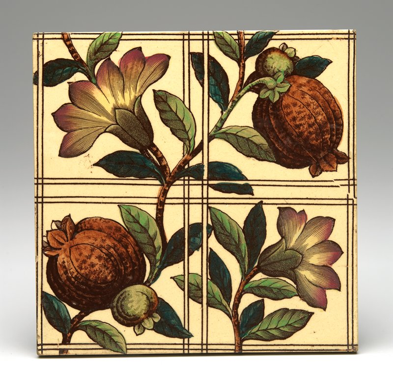 one branch with 2 pomegranates and flower, another branch with flower in one corner; grid design; multicolored transfer decoration on cream ground