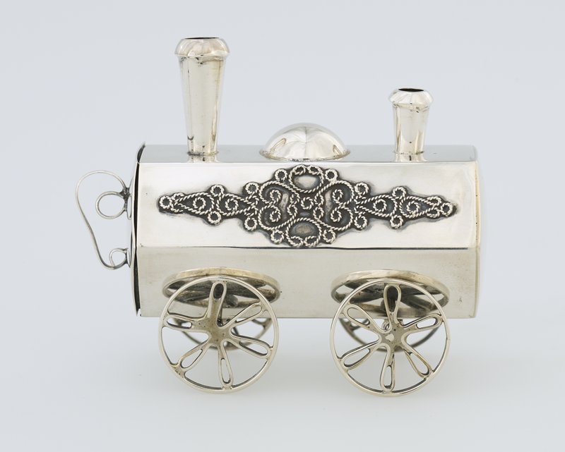 Spice box in the form of a locomotive. Hexagonal body; silver wire scrolls on each side; 2 smokestacks; 2 movable axels with floriform spokes