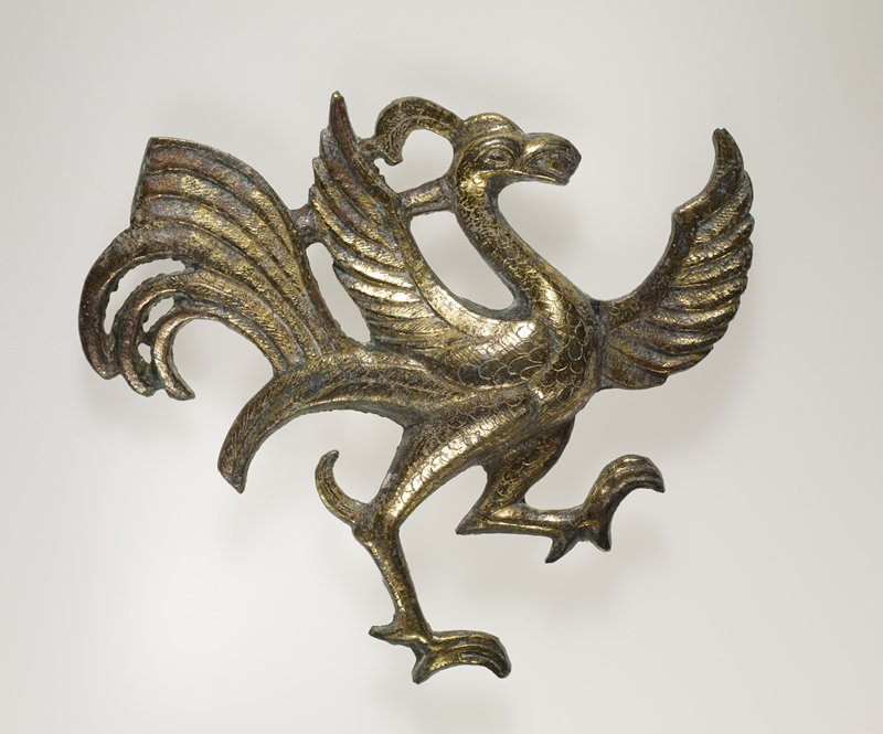 prancing bird with wings outstretched; long tailfeathers; facing R