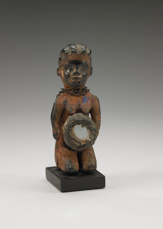 female figurine kneeling with arms hanging free of the body; large mirrored abdominal container; glass eyes; furrowed coiffure; reddish brown with an encrusted surface and areas of glossy black patina; traces of blue pigment on chest