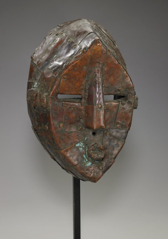 deep, heavy mask pierced through the upper lip for cord suspension; covered overall with thin overlapping plates of copper fastened to the wood with copper nails; worn surface with areas of glossy patina
