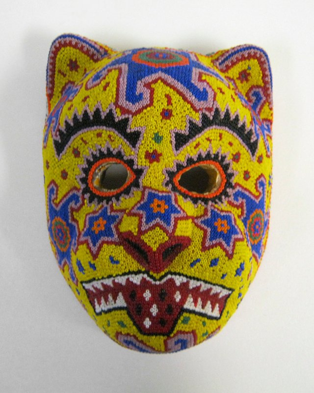 wood form of cat face covered overall in multicolored beads; yellow ground