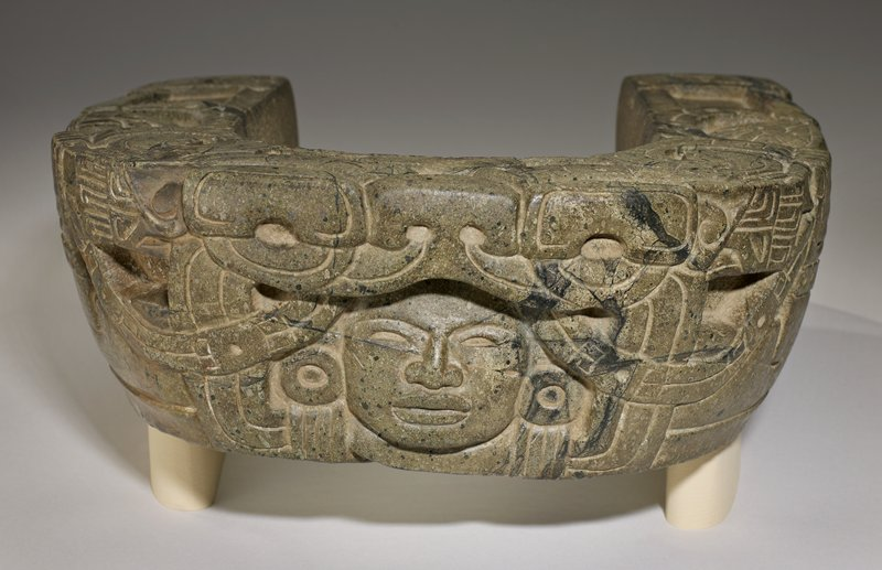 Carved stone yoke with design of a crouching man, his head in the jaws of a monster, gripping a snake. The corners are finished with men's heads in monster's jaws. Serpentine.