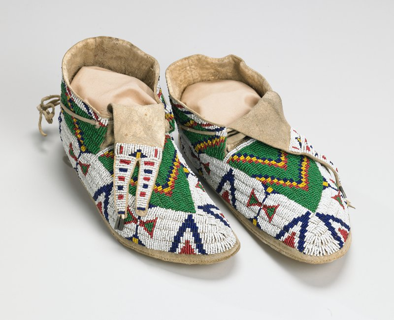 rawhide soles; tanned uppers; split tongues trimmed with tin cones; tops beaded overall with geometric designs