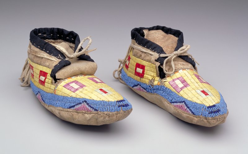 rawhide soles; tanned uppers; black cloth on collars around ankles; tops decorated with porcupine quills in square motifs; band of beading with triangles around edges