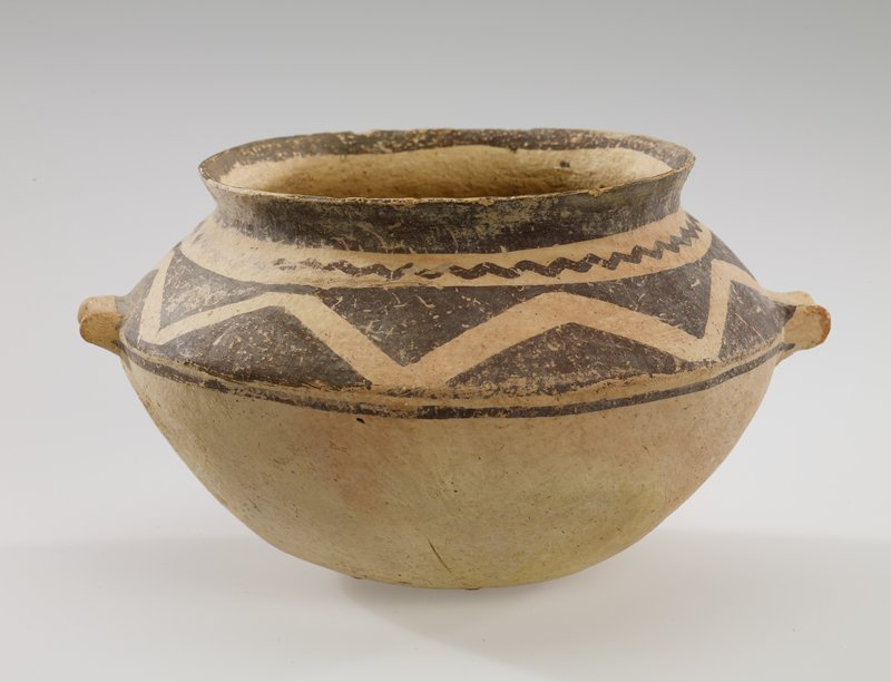 rounded bottom; sloping shoulder coming to a point; 2 pairs of decorative protrusions at shoulder; light tan clay decorated with brown bands of triangles, brown zigzags and brown bands at shoulder