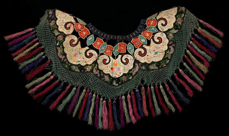 """openwork design; black collar embroidered with pink flowers loosely stitched with bead bands and thread loops to separate """"petals"""" of green and orange, embroidered with flowers; """"petals"""" loosely attached to body with three complete and two partial white scrolls embroidered with flowers and butterflies; woven black ribbon with dragons and flowers below; loose green net-like border at bottom trimmed in multicolored thread tassels"""