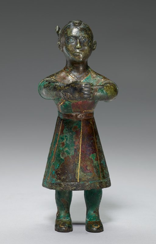 standing male figure with outstretched arms; one hand grasping opposite wrist; green patina; mounted on stand