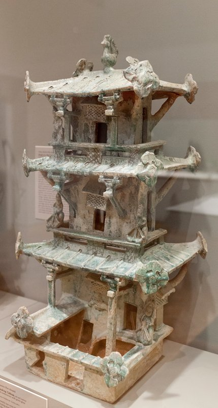 3-level tower with balconies; 4 figures with crossbows; roofs edged with large floral forms; bird at top of roof; green glaze