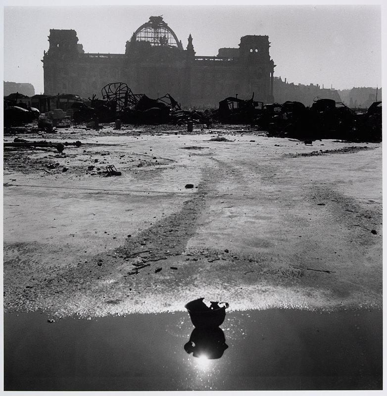 large building with ruined dome in background; debris, rubble and twisted metal in middle ground; puddle with overturned helmet with holes in foreground