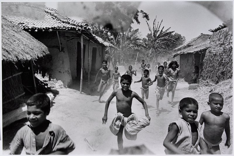 children running down a path between huts; palm trees in background