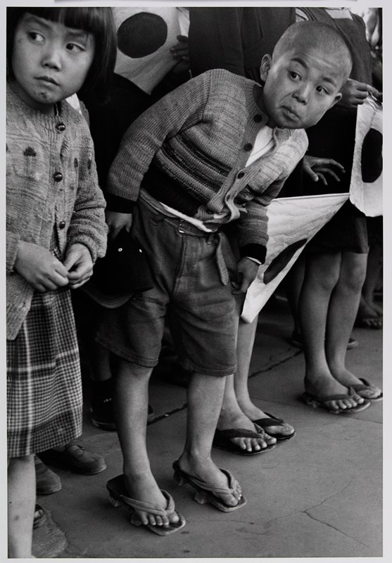 little boy wearing a sweater and shorts at center, leaning forward; little girl at L; bodies and legs of other figures in background