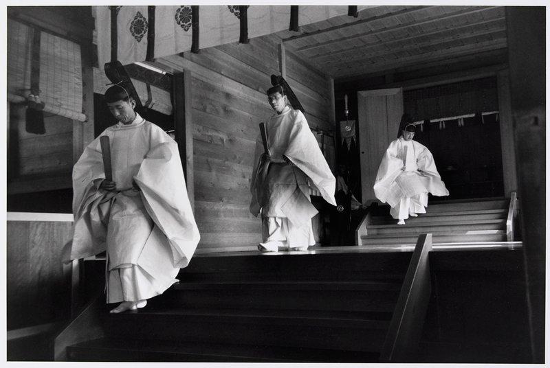 3 men in kimonos, wearing hats, descending 2 short flights of stairs in wood-paneled passage