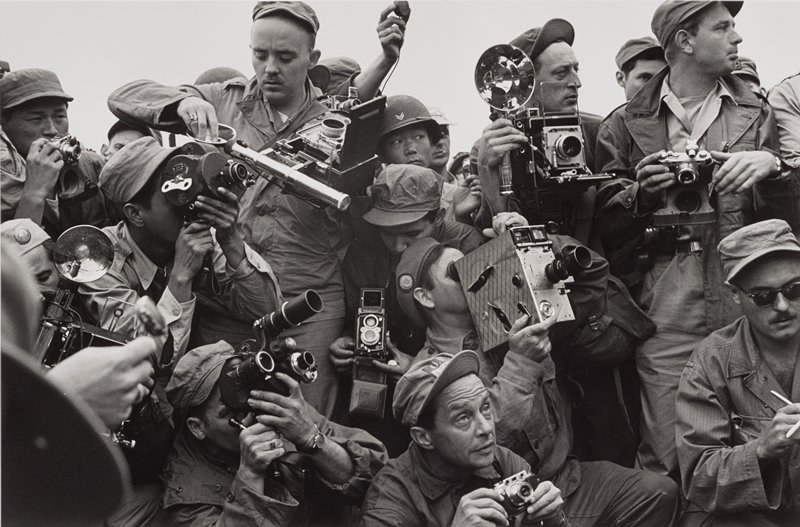 crowd of men with cameras, all dressed in fatigues