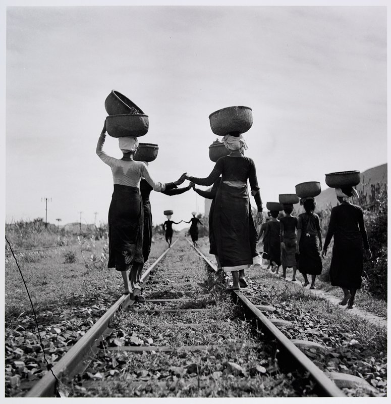 group of women carrying baskets on their heads; 3 pairs of women hold hands and walk on railroad tracks; line of women at R