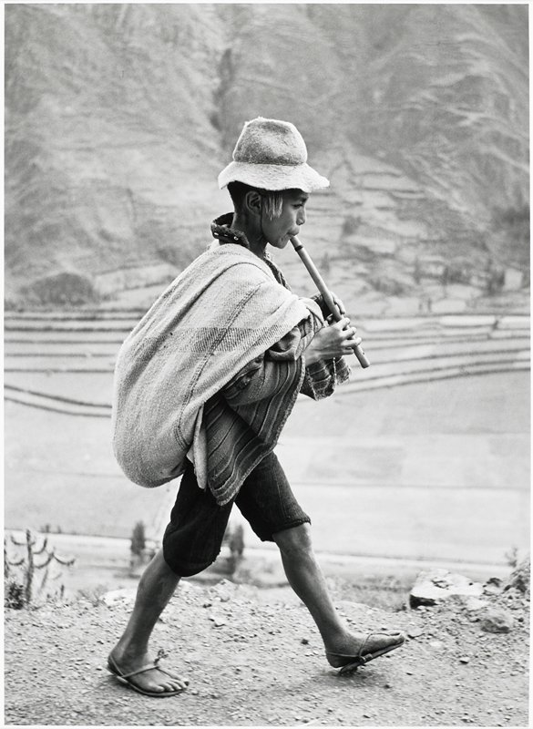 walking boy wearing sandals, short pants and a felt hat, playing a flute
