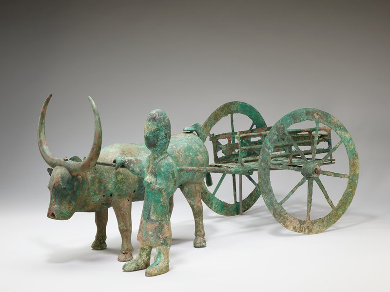 green ox with attachable cart consisting of yoke, 2 side rails and 2 wheels, with accompanying free-standing farmer