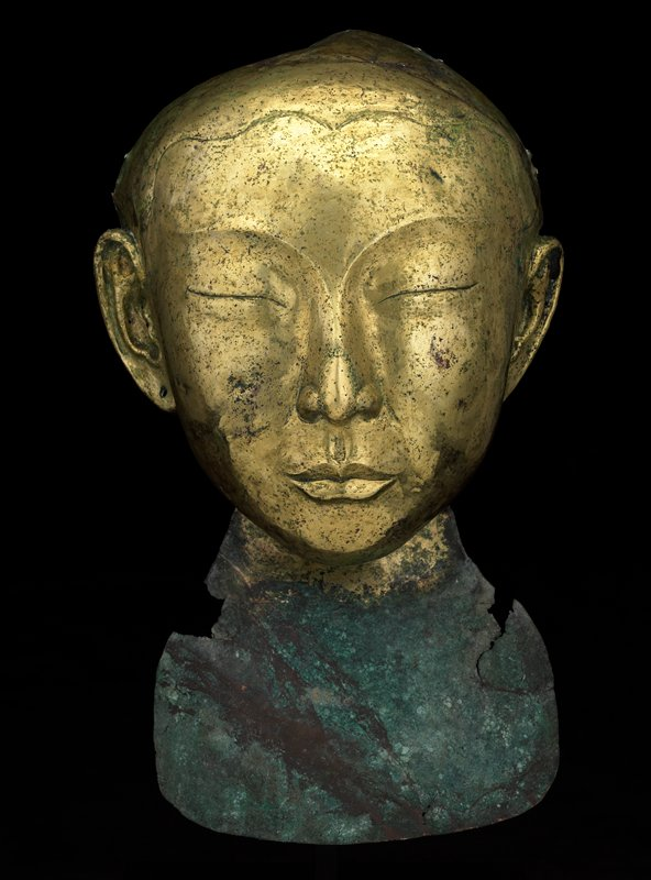 face mask of person with closed eyes; pierced ears; delineated hairline; bronze, with bib attached to neck area in green-blue and brown patina