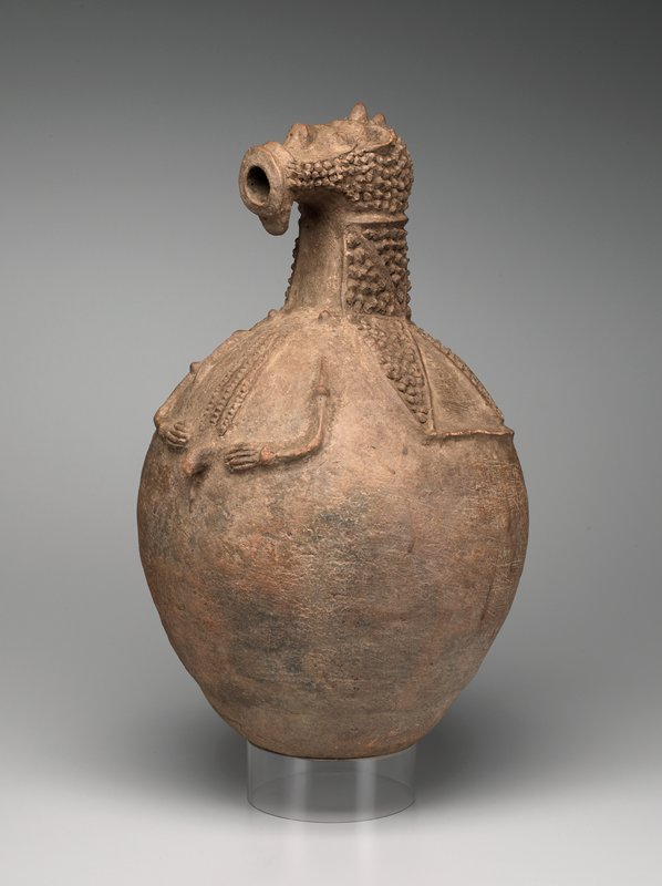 round-bodied vessel with abstracted human neck and pointed head with circular open mouth for spout; small relief arms on stomach