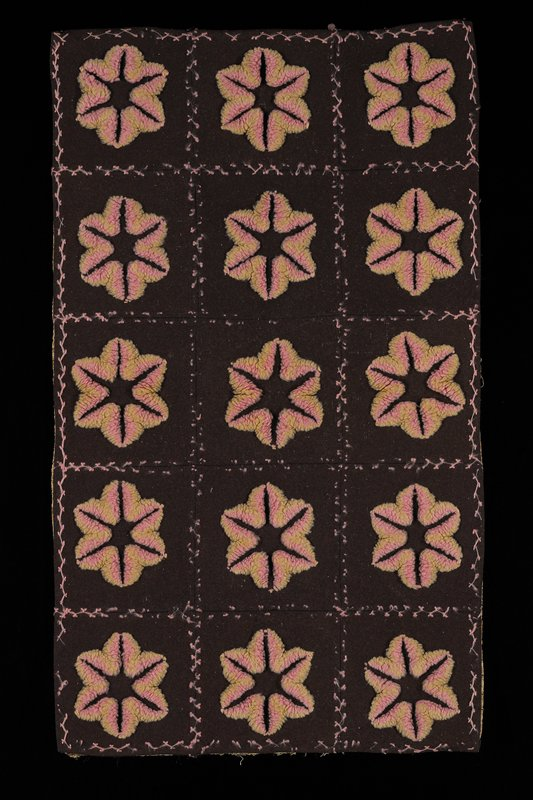 15 brown squares with pink and green tufted floral shapes at center of each; pink stitching between; tan, blue and green brocade backing