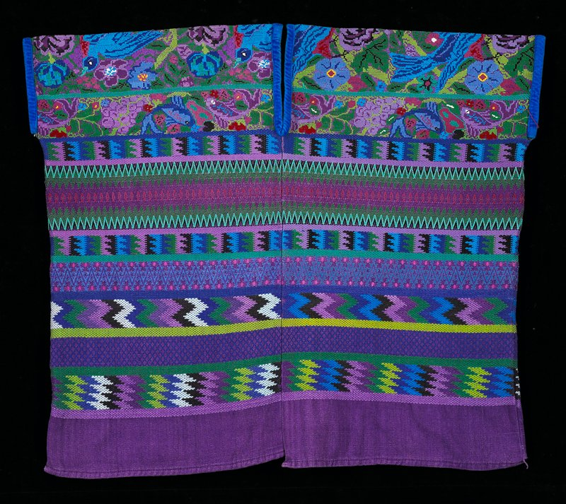 Two-panel huipil; full brocade in horizontal geometric patterns; supplementary weft patterning on sholders; Magenta ground cloth with patterning in many colors; design of flowers fruit, birds, and foliage in blue, rose, yellow and black; blue velvet edges the neckline and armholes. Textile - Woven Fabirc