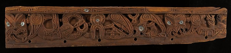 wood panel carved with organic design in curvilinear shapes with several nailed-in shells; reddish finish