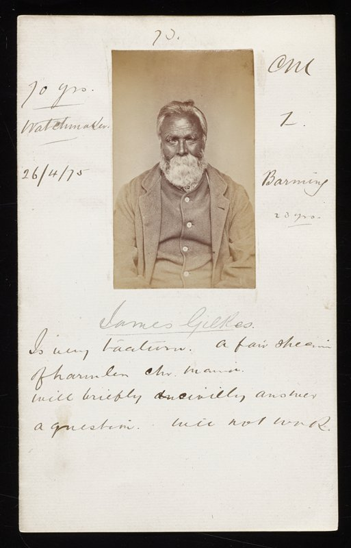 portrait of a man with dark skin and thick white beard and moustache, wearing a suit jacket and vest; photo glued to folded paper with various pen inscriptions