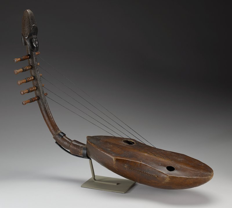 five-stringed harp, strings missing, with a skin-covered sounding box and a curved grooved neck, topped by a carved head with turban headgear
