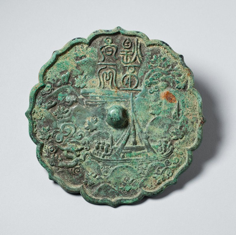 round, flat object with scalloped, pointed edges; raised knob at center; rough ship just R of center knob; stylized waves at L; four Korean characters at top center; green with patina