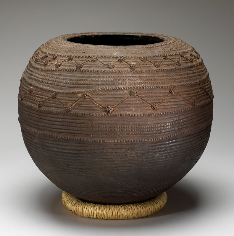 round bodied container; wide mouth; decorated overall with horizontal lines, some with vertical indentations, two zig-zaged rows with small applied pieces at corners of zigzags, and two rows of arcs