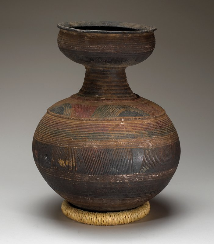 rounded bottom; bulbous body tapering to short neck; neck flares outward to lipped bowl at top; incised overall with linear and arc designs; red, black and green pigments