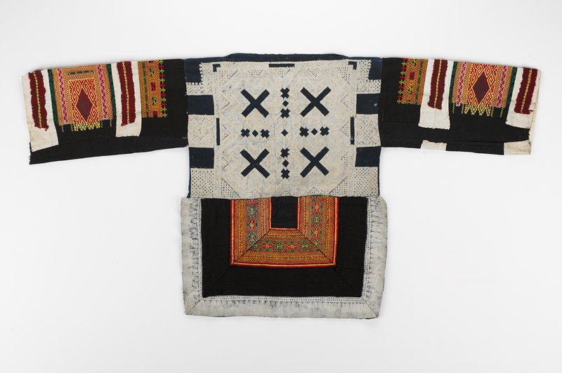boxy shirt; pullover style with long sleeves, long tail; blue body with white geometric dye-resist designs; black and white sleeves and tail with embroidered geometric band designs in red, yellow, green and white