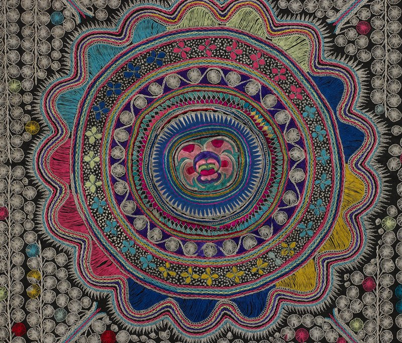 black ground with circular embroidered designs overall in white, pink, turquoise, red, yellow and blues; large central medallion surrounded by wavy border; border on three sides of orange, turquoise, purple fabric and band of tan with green, pink, orange and maroon patterns; fourth side is blue fabric