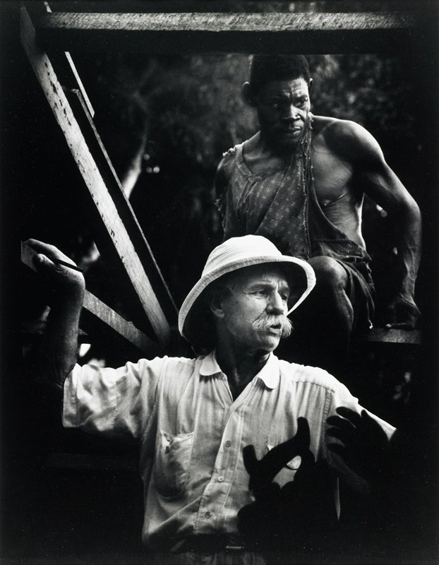 man with bushy white moustache, wearing pith helmet, in foreground; seated black man wearing a torn shirt behind man with moustache