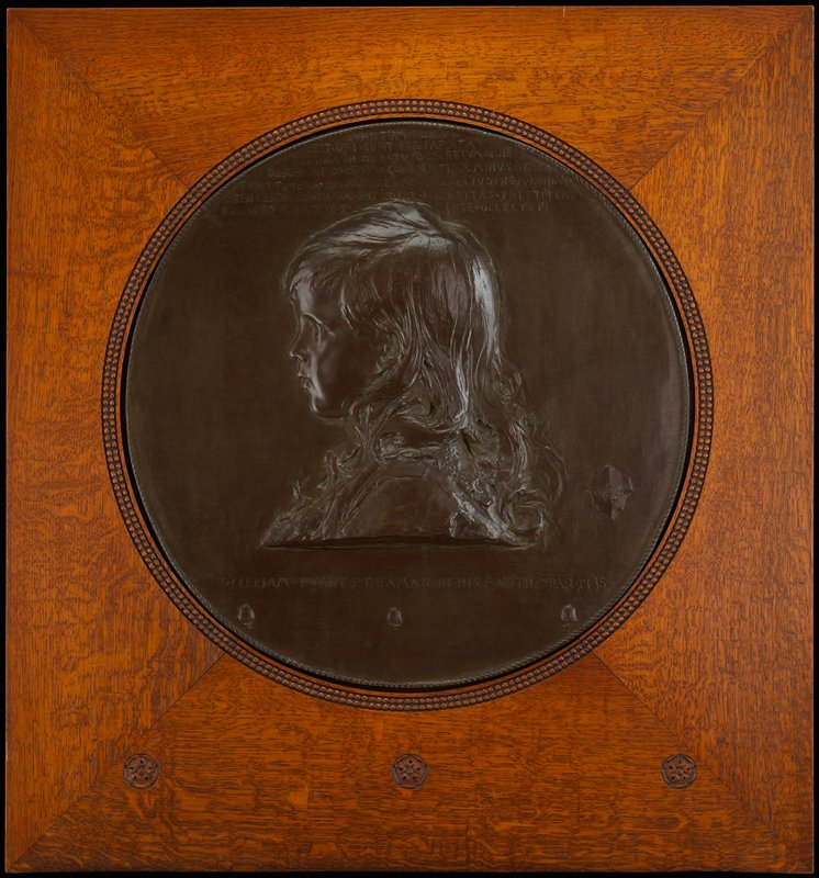 child's head in profile, with long hair; round medallion mounted in square wood frame with three rosettes carved at bottom; seven lines of text at top of medallion; three acorns at bottom of medallion