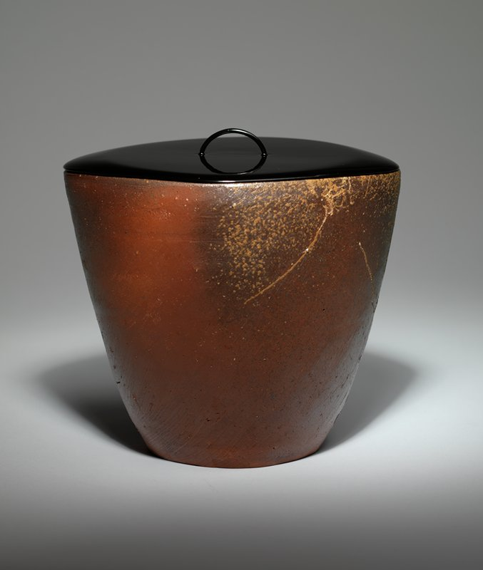 vessel with rounded diamond shape; reddish brown coloring with ochre colored splatters on lip; black lacquer lid with rounded diamond shape and very thin, bowed pull
