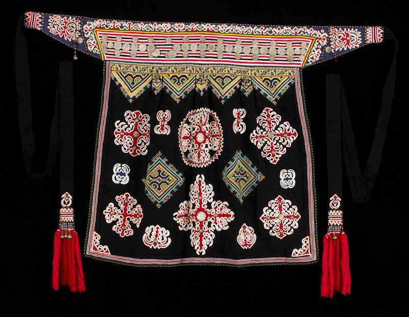 """Black background, white ribbon sewn on red fabric, blue fabric; embroidered motifs (multi-colored); coins sewn, metal bells; two ties with tassles, beads and shells, 64"""" PR and 64"""" PL."""
