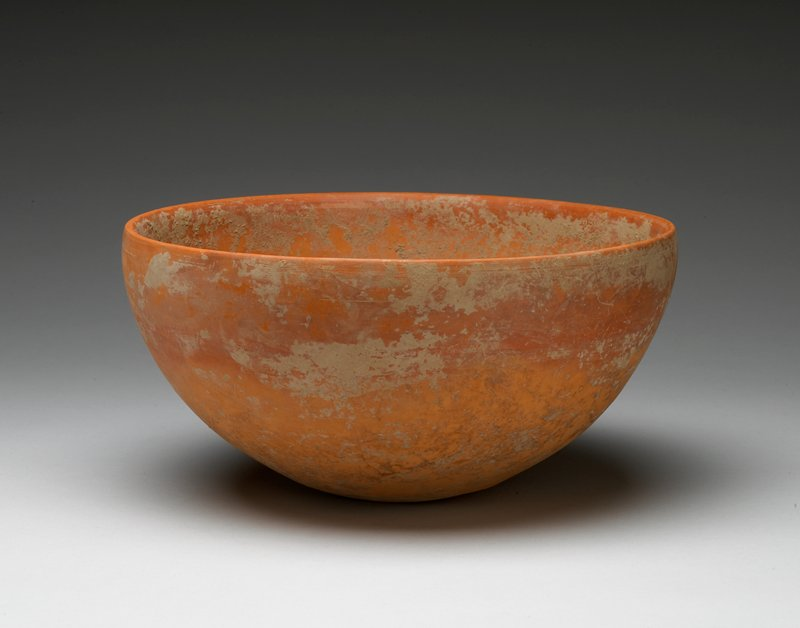 red-orange bowl with tan accretions overall