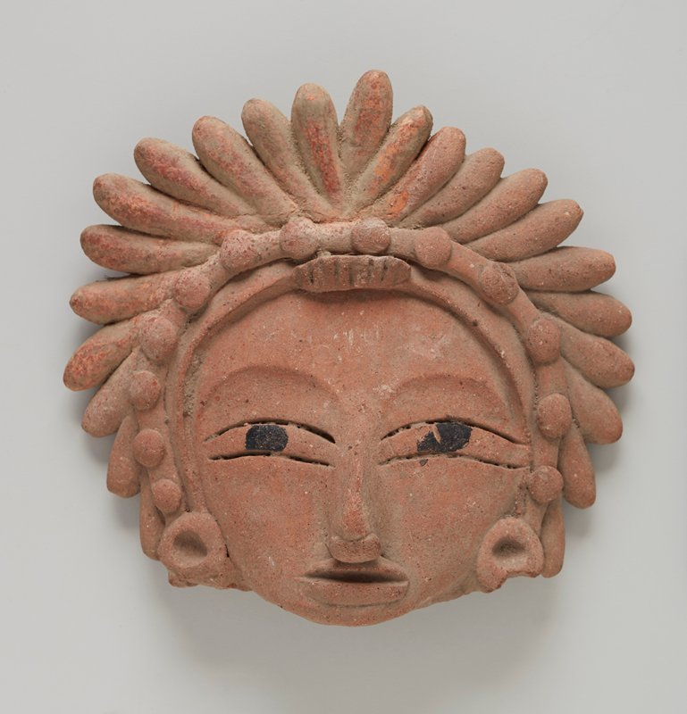 Head with spiky headdress made of rolls and balls of clay. The eyes are long and narrow with painted eyeballs. Wide sweeping brows, long, high-bridged nose, and mouth with full lower lip. Solid disk earrings with depression in center. One earring chipped at lower edge. Wooden base.