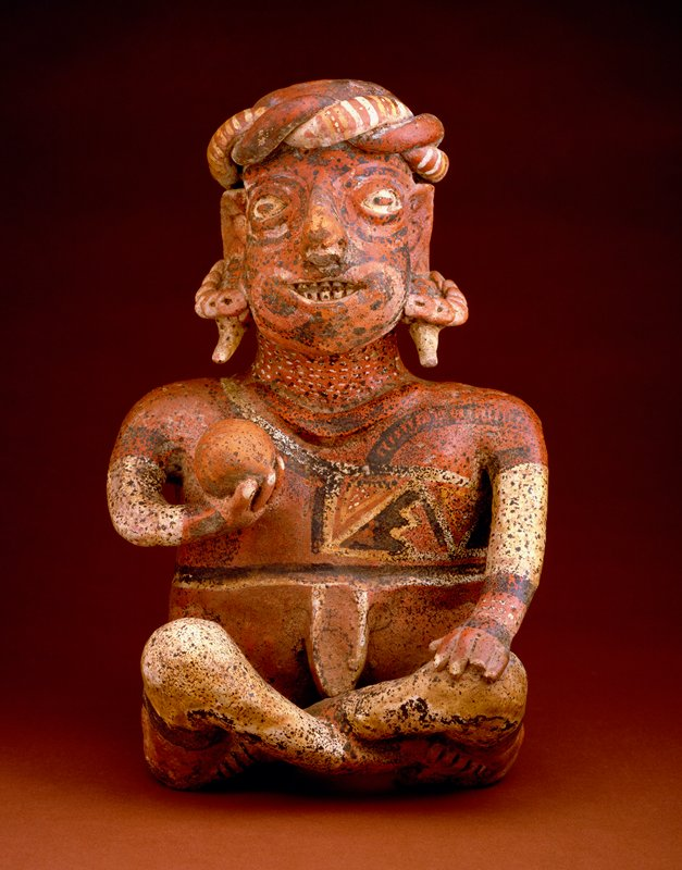 seated ball player; polychrome figure seated with legs crossed, left hand resting on left knee, and ball held in front of breast in right hand; the figure wears a modelled loin cloth, a band at the neck, flat twisted turban, and large ear plugs with pendant ends; the tattooing of face and body represented by geometric designs in polychrome; the face wears the comic expression and tentative smile often found in the figures of Nayarit, and the arms and legs are characteristically stunted