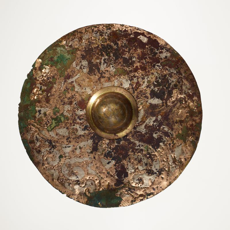 flat, round disc with domed protrusion at center; incised with figures, birds, animals and designs; mounted on black cloth-covered board with L2003.116.4.1