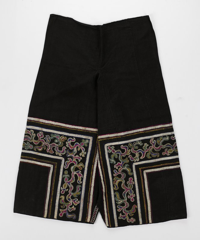 black; wide legs; legs decorated with u-shaped bands of organic multicolored embroidery and striped ribbons