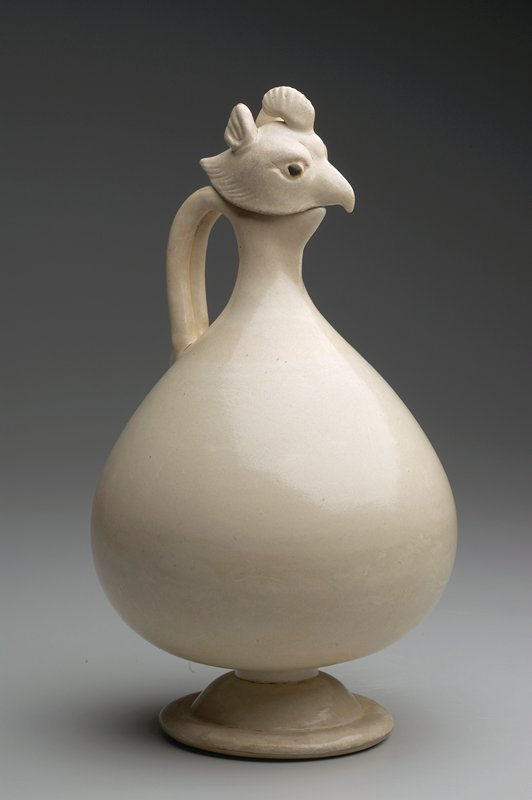 Ewer, with pheasant's head stopper. Pear-shaped body, with tapering short neck and short spout, on domed, spreading foot. The removable stopper, in the form of a pheasant's head, is modelled in full relief with carved details, the double strand handle is also modelled. Buff white porcelain with even, creamy-white glaze.