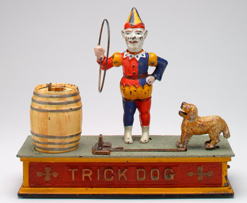"clown in orange, white, yellow, blue hat and costume; yellowish-brown dog on golden lever; light cream-yellow barrel stand on light green, red and yellow rectangular pedestal; ""TRICK DOG"" on front side of pedestal with design on its either side"