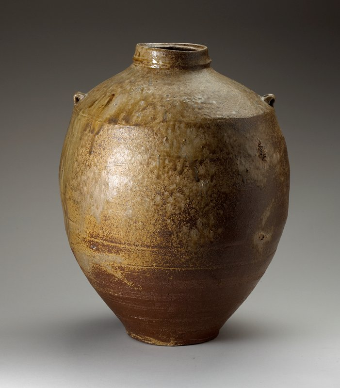 large vessel with bulbous body on small foot; sharp shoulder; two very small decorative handles; ring mouth; brown